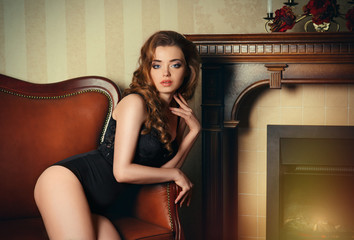 Sexy girl sitting on a brown leather vintage couch.