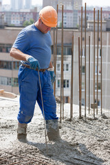 Construction worker compacting ready-mixed concrete