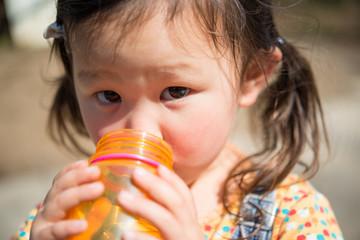 水筒で水を飲む少女