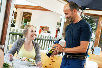 waiter serving young woman in restaurant