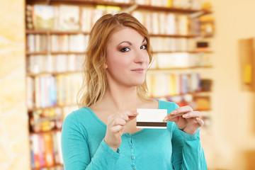 junge blonde Frau hält Geldkarte