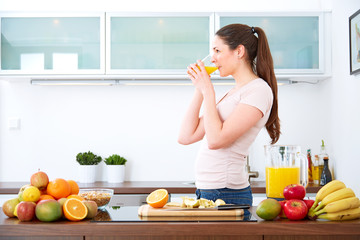 Young woman drinking a glass of orange Juice in the kitchen.II