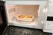 View of open microwave oven with delivery service food inside - 79973538