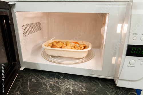 View of open microwave oven with delivery service food inside