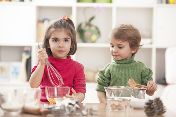 Children playing in the kitchen and learning how to bake