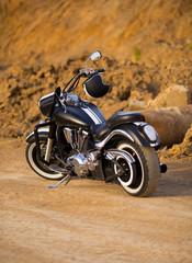 Big, clean, black and unknown chopper bike in desert
