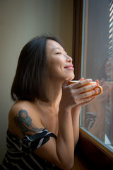 Asian woman close eyes feels positive with orange cup