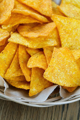 tortilla chips in basket on wooden surface