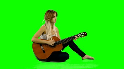 Young beautiful caucasian woman in casual playing guitar. Green