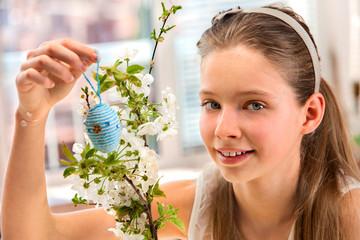 Child hang easter egg on cherry branch.