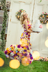 Beautiful woman in a dress of flowers with big birthday cake