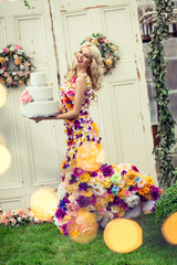 Beautiful smiling woman in a dress with flowers and big cake in