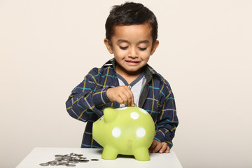 Little kid playing with piggy bank