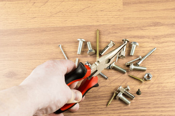 Pliers in hand on a background of various bolts