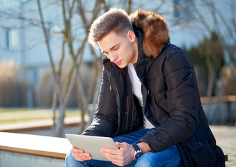 Boy with tablet sitting outside in winter