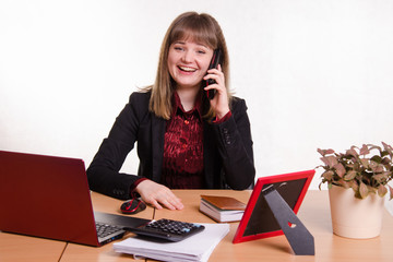 The girl behind the office desk laughing with handset