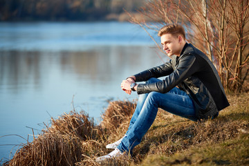 Young man sitting on a pond to relax