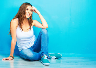 young smiling woman sitting on floor against blue wall