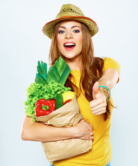 Young woman holding paper bag with vegetarian food.