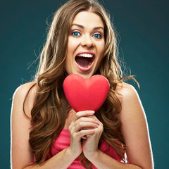 Surprised woman hold red heart.