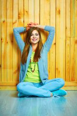 Smiling teenager style dressed girl sitting on a floor with cro