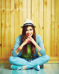 Youth style portrait of young woman sitting on a floor.