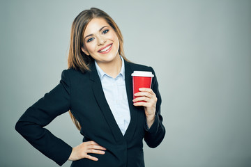 Business woman dressed offise style suit smiling and hold red c