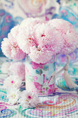 pink flowers in a mug on a beautiful tablecloth.