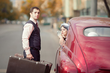 Pretty couple with the trunk near the vintage car
