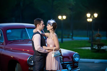 Pretty couple near the vintage car on the night city background