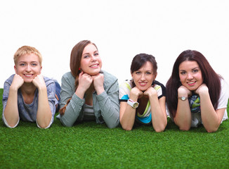 Photo of three woman sitting on grass while looking