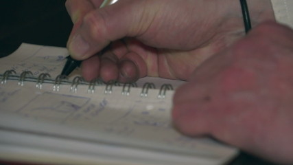 Man's hand with a pen made records in the notebook