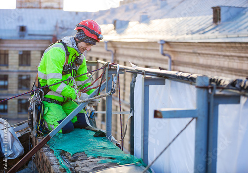 Industrial climber on a roof of a building - 79982383