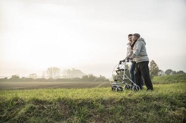 Älterer Mann und sein Enkel mit Rollator