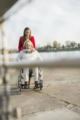 Enkelin helfen ihrer Großmutter im Rollstuhl