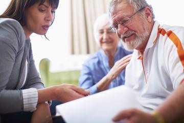 Frau erklärt älterem Pärchen ein Dokument