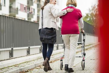 Erwachsene Enkelin hilft ihrer Großmutter zu Fuß mit Rollator, Rückansicht