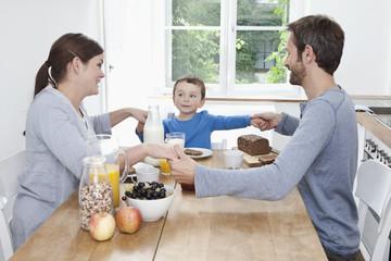 Deutschland, Bayern, München, Familie, die zusammen frühstückt, glücklich