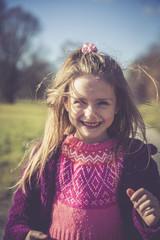 Porträt des lächelnden Mädchen mit rosa Strickpullover