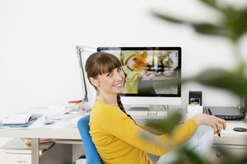 Frau am Schreibtisch mit Foto von Junge auf dem Bildschirm