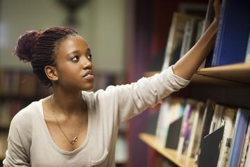 Weiblicher Student in einer Bibliothek am Bücherregal