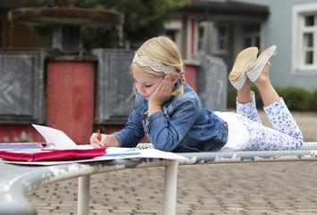 Kleines Mädchen macht Hausaufgaben auf dem Schulhof