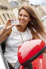 Portrait einer glücklichen jungen Frau, die ihre Fahrerlaubnis zeigt
