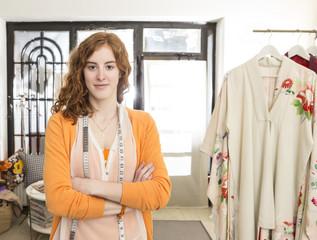 Porträt der lächelnden Mode-Designerin mit Maßband in ihrem Atelier