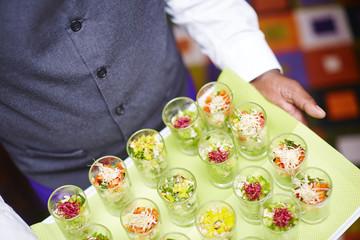 Kellner trägt Tablett mit Salaten in Gläsern