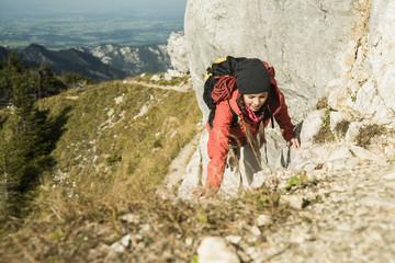 Österreich, Tirol, Tannheimer Tal, junge Frau wandert auf Felsen