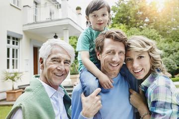 Deutschland, Heese, Frankfurt, Junge Familie mit Großvater vor der Villa