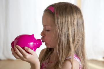 Mädchen küsst ihr rosa Sparschwein