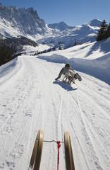 Schweiz, Graubünden, Savognin, Junge (8-9) rodelt, Rückansicht