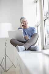 Deutschland, Bayern, München, älterer Mann mit Handy und Laptop, lächelnd
